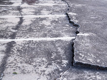 Concrete Floor Or Cement Road On Old Parking Lot Damaged And Cracked From Ground Subsidence.