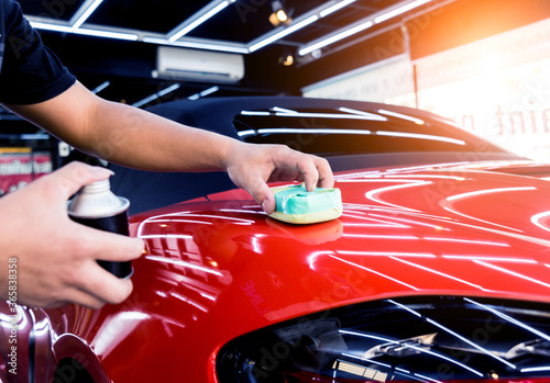 Fototapeta Car service worker applying nano coating on a car detail