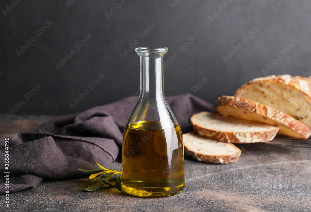 Fototapeta Bottle of tasty olive oil and bread on dark background