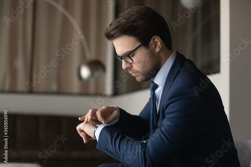 Obraz na plátně Serious caucasian businessman in formal suit glasses check time on modern smartw