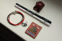 A Composition Of A Chinese Red Tortoise Figurine, A Black And White Pen, A Bracelet With A Yin Yang Symbol And A Metal Magnet With A Chinese Building On A White Background.