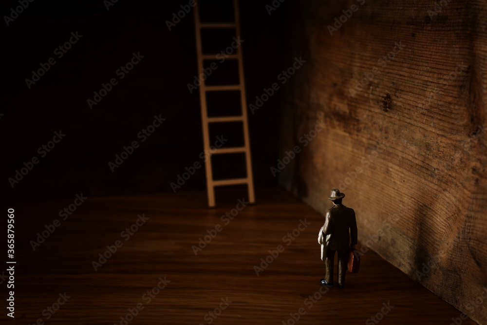 Fototapeta business concept picture of challenge. A man stands infront of a a ladder. Problem solving and decision making.