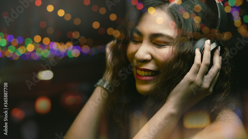 Blurry and colorful of woman wearing headphone closed her eyes and smiling while listening music, Mood of relaxation young woman lifestyle enjoy with streaming entertainment media Canvas Print