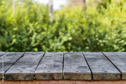 Slika na platnu Grey wooden picnic table top at sunny summer day on blurred background of green