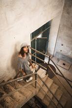Modelo De Ropa Gris, Gorra De Visera Plana Gris, Zapatillas Blancas Y Pelo Largo Baja Una Escaleras En Una Nave Industrial Abandonada De Color Crema