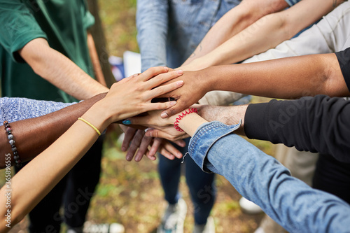 Fototapeta close-up photo of diverse people's hands gathered together, african american and caucasian people as one union. various ethnicities are friends all over the world obraz