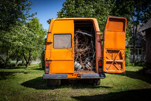 Rear View Of An Old Orange Vintage Van With The Right Back Door Opened Filled With Scrape Metal, Waiting To Be Recycled In A Natural Green Yard With Trees And Lawn Under The Summer Sun