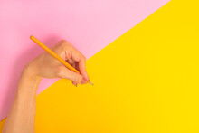 The Left Hand Is Holding A Pencil And Is About To Write Something On A Bright Pink-yellow Background. International Left-handers Day On August 13.