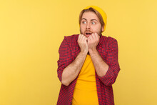 I'm Afraid! Scared Hipster Coward Guy In Beanie Hat And Checkered Shirt Looking Terrified Panicking Frightened, Noticing Something Terrible, Phobia. Indoor Studio Shot Isolated On Yellow Background