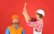 canvas print picture - Couple making repair at home. Home Renovation. Rub in. Couple knocking head with hammer. Clearly explain. Intelligibly concept. Couple renovating apartment together. Man and woman wear safety helmet