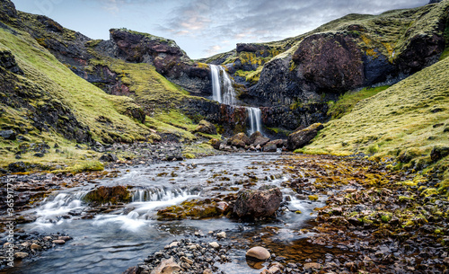 Slika na platnu Amazing Icelandic landscape with Powerful waterfall in basalt canyon with green grass and tipical lava moss