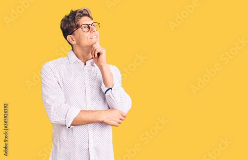 Young handsome man wearing business clothes and glasses with hand on chin thinking about question, pensive expression Tapéta, Fotótapéta