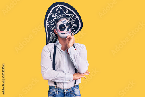 Fényképezés Man wearing day of the dead costume over background with hand on chin thinking about question, pensive expression