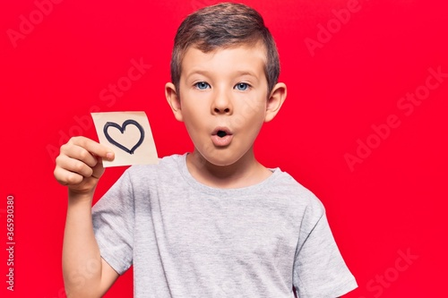 Cute blond kid holding heart reminder scared and amazed with open mouth for surprise, disbelief face