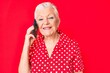 canvas print picture - Senior beautiful woman with blue eyes and grey hair having conversation talking on the smartphone looking positive and happy standing and smiling with a confident smile showing teeth