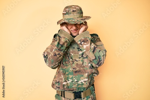 Fotografie, Tablou Young handsome man wearing camouflage army uniform covering ears with fingers with annoyed expression for the noise of loud music