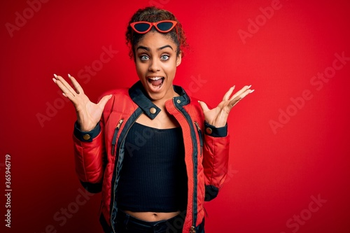 Beautiful african american girl wearing red jacket and sunglasses over isolated background celebrating crazy and amazed for success with arms raised and open eyes screaming excited Wallpaper Mural