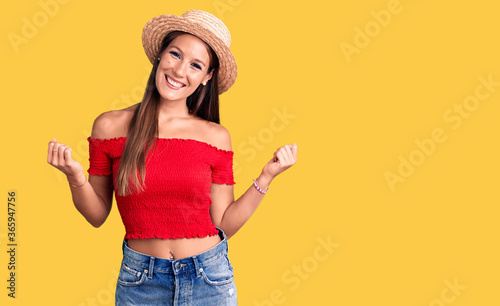Young beautiful hispanic woman wearing summer hat screaming proud, celebrating v Canvas Print