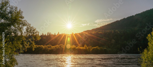 sunset on the river. Reflection of the yellow sun in the water. beautiful Siberian landscape in the forest #365960929