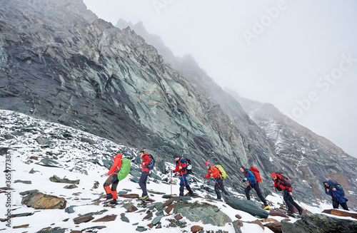 Side view of hikers team with backpacks, trekking sticks walking on rocky path at the bottom of mountain, walking one after another on hillside road covered with snow Fototapeta