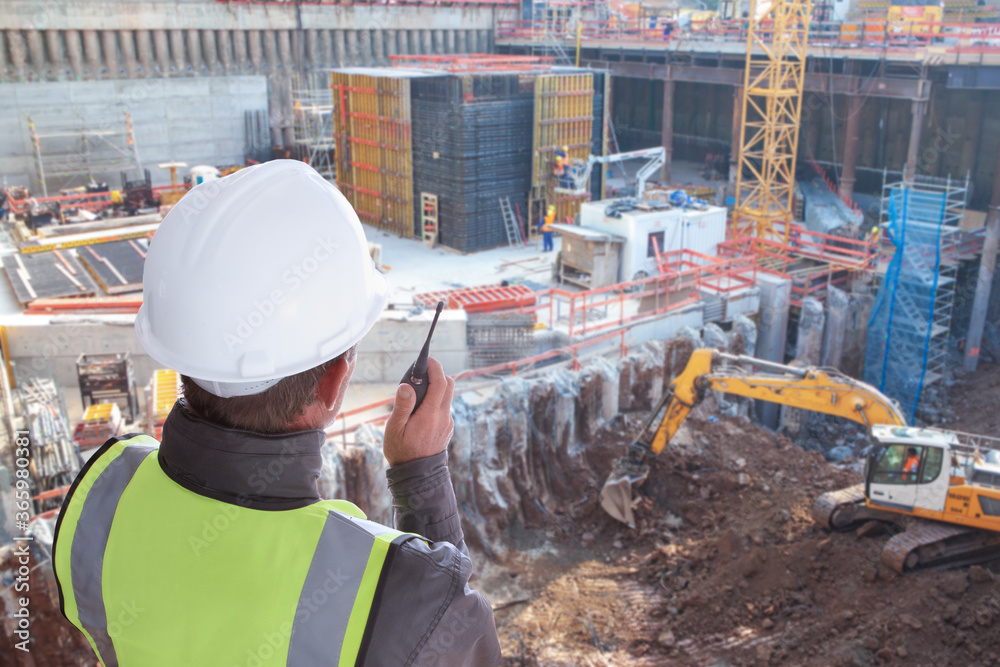 Fototapeta construction worker or civil engineer or architect or foreman with hard hat and safety vest at major construction site with crane and digger supervising with walkie talkie