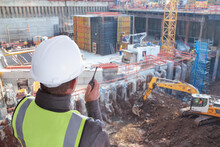 Construction Worker Or Civil Engineer Or Architect Or Foreman With Hard Hat And Safety Vest At Major Construction Site With Crane And Digger Supervising With Walkie Talkie