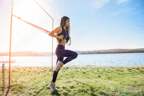 sport woman doing  training outdoors with TRX at daytime Fototapet