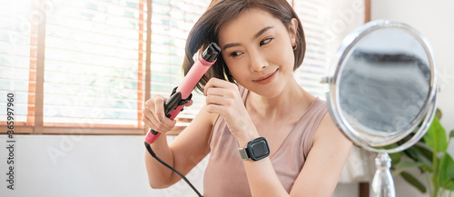 Slika na platnu Portrait of asian woman curling her hair with curler straightener home smart obj