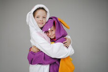 Two Beautiful Girls Dressed As Rabbit And Dragon Posing In Front Of Grey Background