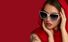 Portrait Of Gorgeous Sexy Woman With Luxurious Make-up In White Sunglasses And Red Headscarf On Red Background. Copy Space For Text