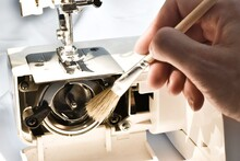 Cleaning And Preparation Of Sewing Machine. A Woman Uses A Brush To Clean The Inside Of The Sewing Machine From Dust.
