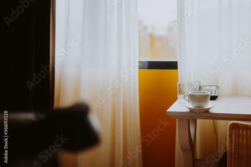 Blick in ein Zimmer mit Tisch Kaffeetasse und Telefon im Hintergrund ein Fenster mit Vorhängen