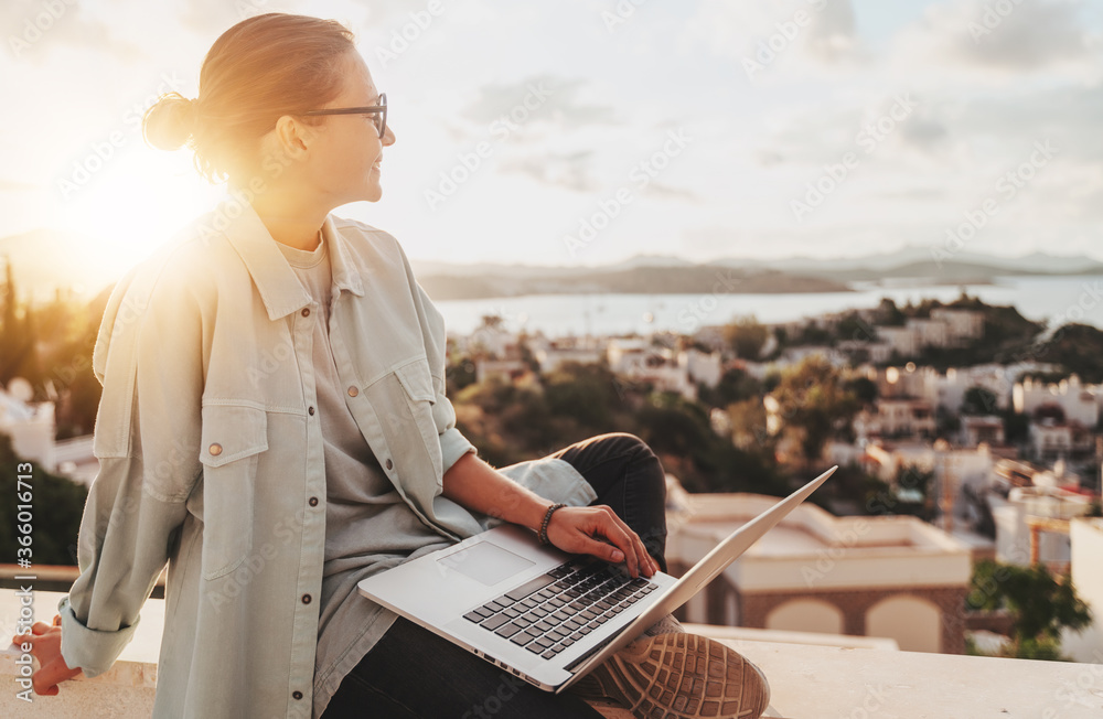Fototapeta Beautiful curly young girl with glasses working on a laptop with a city view at sunset. Modern technologies, urban lifestyle. Freelance and online education
