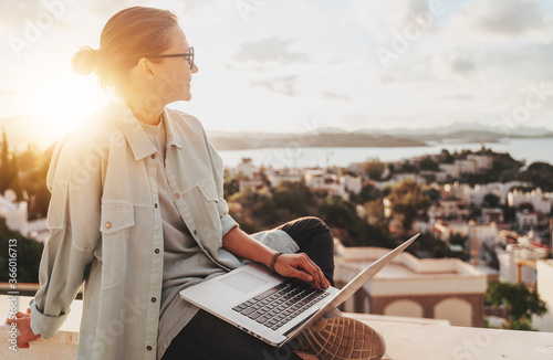 Fototapeta Beautiful curly young girl with glasses working on a laptop with a city view at sunset. Modern technologies, urban lifestyle. Freelance and online education obraz
