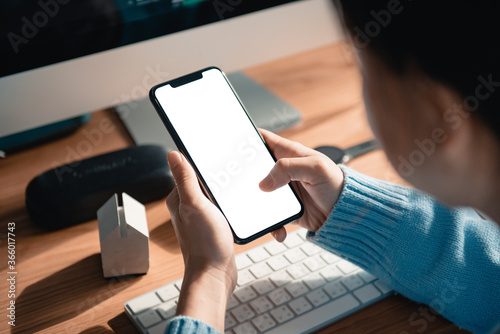 Photo Hand touching mobile smartphone with blank white screen on the desk in the office, copy space
