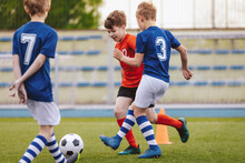 Youth Junior Athletes In Red And Blue Soccer Shirts. Sports Education. Kids Football Players Kicking Ball On Soccer Field. Sports Soccer Horizontal Background. Spectators On Stadium In The Background