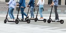 Friends Having Ride On Motorized Kick Scooters