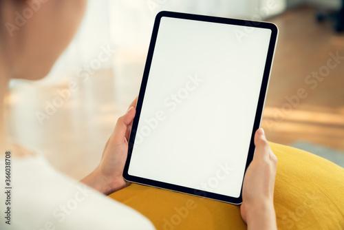 Fototapeta Hand holding digital tablet mockup of blank screen. Take your screen to put on advertising. obraz