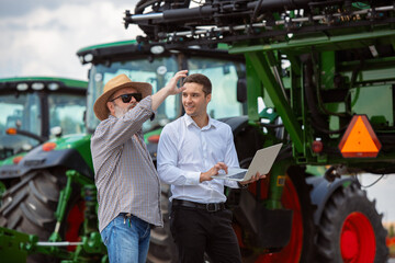 Professional farmer with a modern combine at field in sunlight at work. Confident, bright summer colors. Agriculture, exhibition, machinery, plant production. Senior man near his tractor with investor