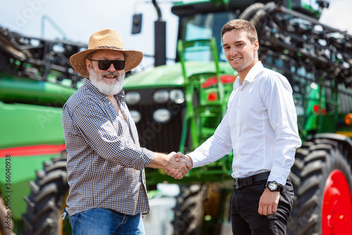 Fototapeta Agreement. Professional farmer with a modern combine in sunlight at work. Confident, bright summer colors. Agriculture, exhibition, machinery, plant production. Senior man near his tractor with obraz