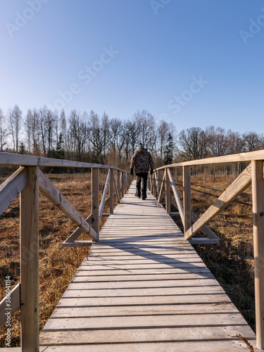 a male figure on a wooden footbridge Fototapet
