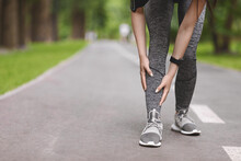 Young Female Runner Suffering From Shin Splints While Jogging In Park