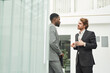 Portrait of two successful businessmen wearing suits chatting while standing outdoors by office building, copy space