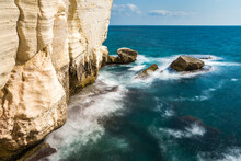 White Chalk Cliffs Of Rosh HaNikra Grottoes, On The Northern Border Of Israel, With Turquoise Waters Of The Mediterranean Sea And An Israeli Navy Border Patrol Boat In The Background; Western Galilee