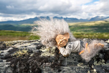 Beautiful Peaceful And Sleeping Troll Girl Figure Relaxing Outdoors With Mountain Scenery In The Background.