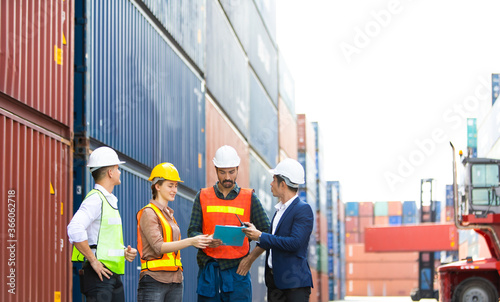 Fotografia, Obraz Group of professional dock worker and engineering people wearing hardhat safety helmet and safety vest standing and working at container yard port of import and export