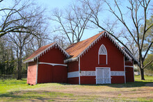 A Ornately Trimmed Southern Style Vintage Red Barn With White Latticework Doors And Windows In An Sunny Autumn Field