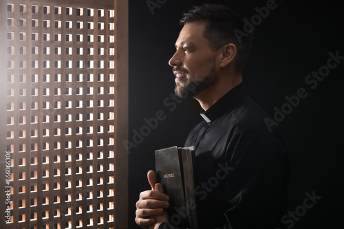 Fototapeta Male priest in confession booth