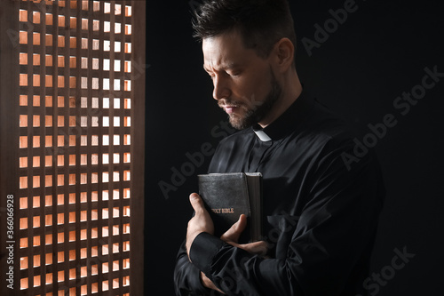 Male priest in confession booth Canvas Print