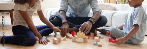 Naklejka premium Zamknij się szeroki baner widok na panoramę figlarnego afroamerykańskiego ojca z małymi dziećmi siedzącymi na podłodze bawiąc się cegłami, biracial tata z małymi dziećmi konstruuje z drewnianych klocków w domu